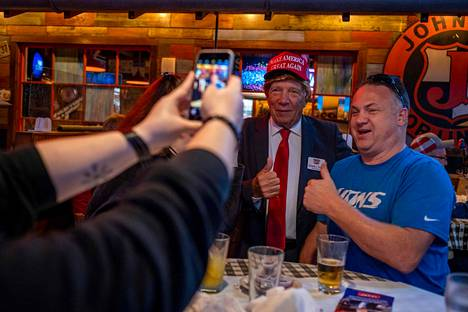 Donald Trumpin kannattaja poseerasi Trump-naamariin pukeutuneen kaverinsa seurassa vaalivalvojaisissa Floridassa tiistaina.