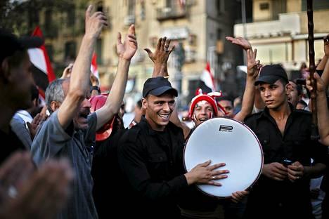 Poliisit juhlivat syrjäytetyn presidentti Mursin vastustajien kanssa Tahririn aukiolla lauantaina.