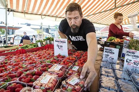 Torikauppias Timo Lauronen asetteli myyntiin mansikoita, parsaa ja nauriita Kuopion torilla perjantaina.