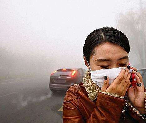 Nainen suojautui ilmansaasteilta Kiinan Harbinissa maanantaina. Pienhiukkasten määrä ylitti WHO:n rajan monikymmenkertaisesti.