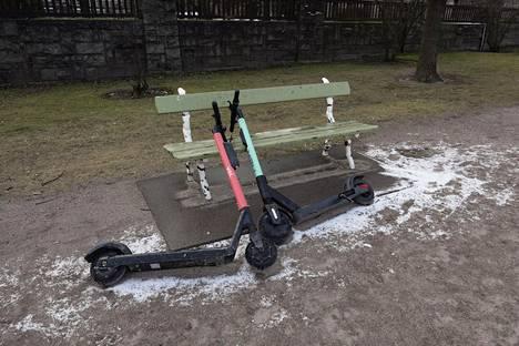 29. helmikuuta: Vuokrattavat sähköpotkulaudat makasivat puistonpenkkiä vasten, ja ympärillä oli hieman valkoista lumisadekuuron jäljiltä.
