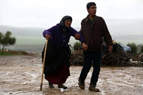 Mies auttoi vanhaa naista pommisuojaan Qastal Koshkin kylässä Afrinin kaupungin pohjoispuolella perjantaina.