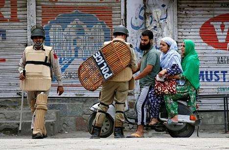 Poliisi tarkisti henkilötodistuksia ulkonaliikkumiskiellon aikana Srinagarissa Intiassa maanantaina.