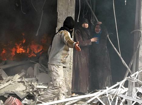 Mies näytti kahdelle naiselle tietä ulos hallinnon ilmaiskun tuhoamasta rakennuksesta Aleppossa torstaina.