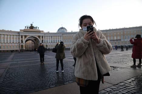 Kiinalaisturistit ottivat valokuvia Eremitaasin edustalla Pietarissa tammikuun lopulla.