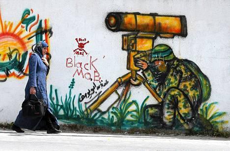 Palestiinalainen nainen käveli torstaina seinämaalauksen ohi Etelä-Gazassa.