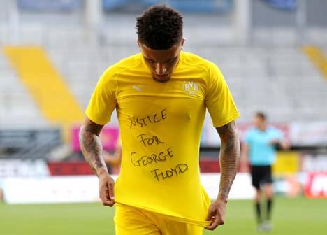 Dortmundin englantilaistähti Jadon Sancho esitteli paitaansa kirjoitettua viestiä Paderbornia vastaan tekemänsä maalin jälkeen sunnuntaina pelatussa Bundesliigan ottelussa.
