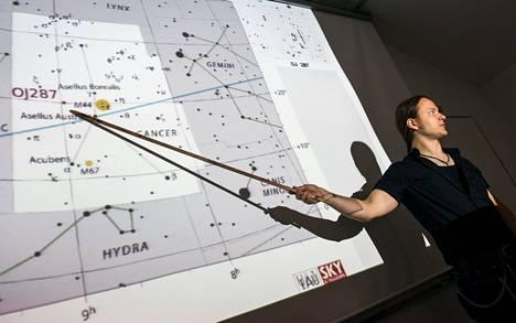 Pauli Pihajoki osoittaa Tuorlan observatorion luentosalissa, missä taivaankannella on kohde OJ287, kahden mustan aukon pari.