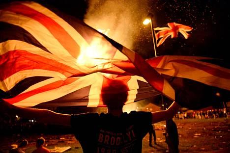 Mies heilutti Britannian lippua kokon edessä Oranialaisen päivänä 12. heinäkuuta, joka juhlistaa protestanttisen Vilhelm III Oranialaisen voittoa Jaakko II:sta Belfastissa.