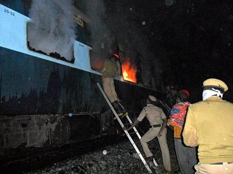 Pelastustyöntekijä yritti saada palavan junavaunun ikkunan auki perjantaina.