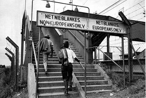 """Junat, bussit, vuokra-autot, jokaista on kahta lajia, valkoisille ja värillisille. Teksti portaiden yllä: """"Vain ei-eurooppalaisille""""."""