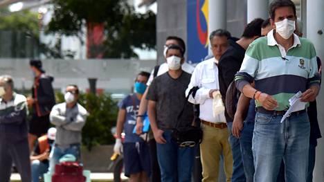 Miehet jonottivat pankkiin huhtikuun kolmantenatoista Kolumbian Bogotassa.
