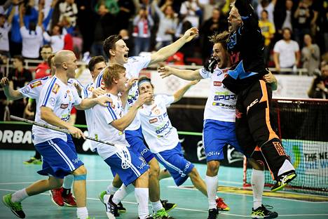 Maalivahti Jarno Ihme (oik.) riemuitsi joukkuetovereineen, kun Suomi voitti salibandyn maailmanmestaruuden Riiassa.