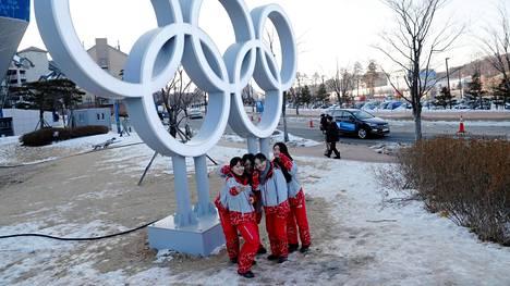 Vapaaehtoiset poseerasivat olympiarenkaisiin nojaten Pyeongchangissa keskiviikkona.