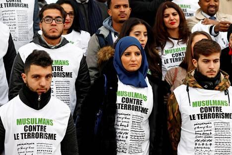 """""""Muslimit terrorismia vastaan"""", luki mielenosoittajien paidoissa marraskuun 13. päivä Pariisissa. Seremoniassa kunnioitettiin niitä 130 ihmistä, jotka kuolivat Isis-järjestön suunnittelemissa Pariisin terrori-iskuissa tasan kaksi vuotta aikaisemmin."""