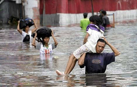 Mies kantoi tytärtään turvaan tulvilta Jakartassa perjantaina.