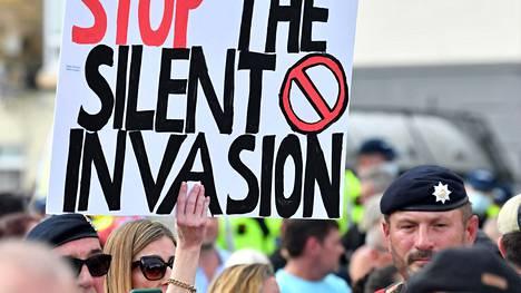 """Maahanmuuton vastaiset mielenosoittajat vaativat """"hiljaisen maahantunkeutumisen"""" pysäyttämistä mielenosoituksessaan Englannin kanaalin kupeessa Doverissa syyskuun alussa."""