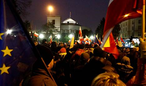 Mielenosoittajia Varsovassa lauantai-iltana. Taustalla näkyy Puolan parlamentti Sejm.
