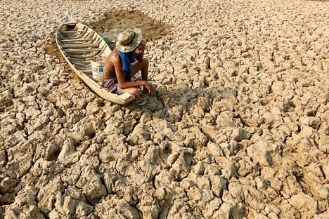 Kalastaja istui tupakoimassa veneessään Bak Angroutin kuivuneella lammella kuivuuden vaivaamassa Kandalin provinssissa Kambodžassa.