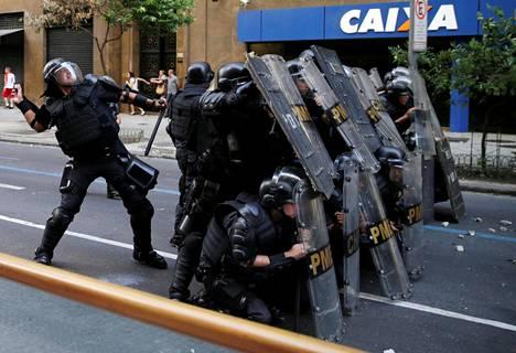 Kilvillä suojautuneen poliisirivistön takana oleva mellakkapoliisi vastaa kivitykseen torstaina Brasilian Rio Janeirossa. Kaupungissa osoitettiin mieltä hallituksen säästötoimia vastaan.