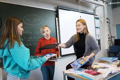 Maria Kuosmanen jakaa oppilailleen kannettavat tietokoneet ja oppikirjoja.