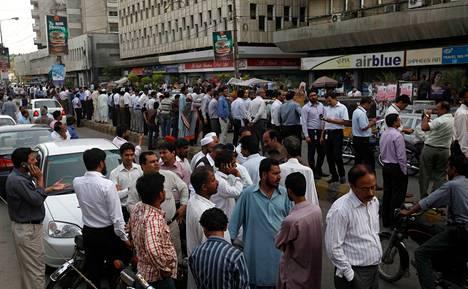 Ihmisiä seisoi kadulla maanjäristyksen ravisteltua toimistorakennusta Karachissa Pakistanissa tiistaina.