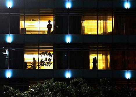 """Ihmiset seisoivat Jakartassa Indonesiassa hotellissa, jonka ikkunassa luki """"Happy New Year""""."""