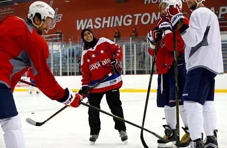 """Arabiemiraateista kotoisin oleva Fatima Al Ali kokeilee jääkiekkoa Washington Capiltalsin järjestämässä """"Kiekkoa kaikille"""" -tapahtumassa keskiviikkona. Opastajina NHL-tähdet Justin Williams (vas.) ja Aleksandr Ovetškin."""