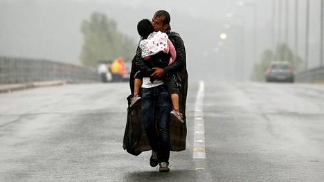Turvapaikanhakija kantoi tytärtään kävellessään Kreikasta Makedoniaan syyskuussa 2015.