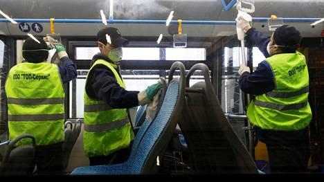 Siivoojat puhdistivat Moskovan kaupunkiliikenteen bussia perjantaina. Desinfioinneilla pyritään estämään koronaviruksen leviäminen.