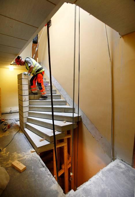 Jaakko Jokiaho asentaa uusia kierreportaita paikalleen Kauniaisissa. Portaikon viereen jää vielä tilaa uudelle hissille.