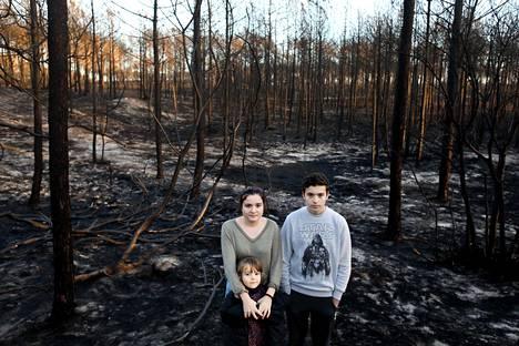 HS haastatteli vuonna 2018 kanteeseen rahaa keränneitä portugalilaissisaruksia Martimia, Cláudiaa ja Marianaa. Kuvassa he seisoivat palaneen Leirian metsän keskellä.