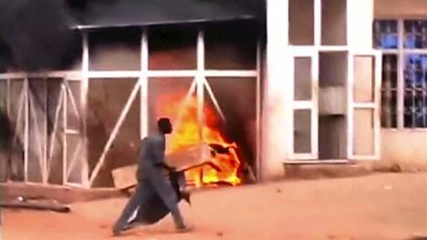 Mies käveli palavan bensa-aseman ohi Khartumissa tiistaina. Kuva kaapattu videolta.