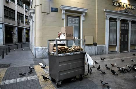 Mies myi leipää Ateenassa Kreikassa, jonka velkojen hoidosta ei EU:ssa vieläkään ole päästy yksimielisyyteen.