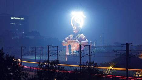 Metrojuna kulki apinankasvoisen hindujumalan Hanumanin  33 metriä korkean patsaan ohi Jhandewalanin aseman vieressä Delhissä tammikuussa.