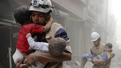 Valkoiset kypärät -järjestön pelastustyöntekijät kantoivat lapsia Aleppossa pommi-iskun jälkeen kesäkuussa.