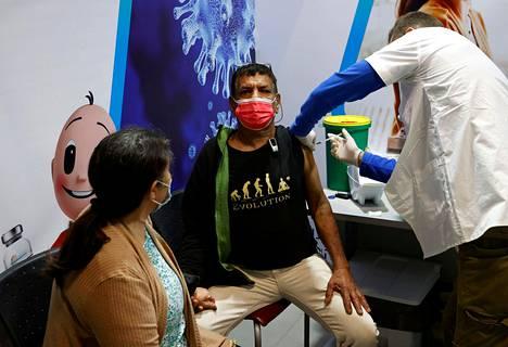 Mies sai keskiviikkona koronavirusrokotteen stadionin rokotuspaikalla Netanyan rannikkokaupungissa Israelissa.