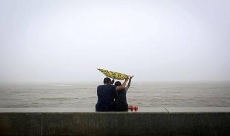 Pariskunta pitelee tuulen mukana tempoilevaa sateenvarjoa Mumbaissa Arabianmeren rannalla. Monsuunisateet riepottelevat Intiaa.