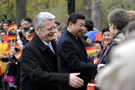 Saksan presidentti Joachim Gauck (vas.) ja Kiinan presidentti Xi Jinping kättelivät Saksassa asuvia kiinalaisia tervetuloseremoniassa Berliinissä perjantaina.