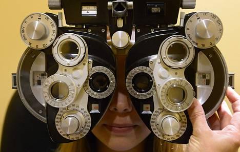 Asiakas näöntarkastuksessa optikolla.