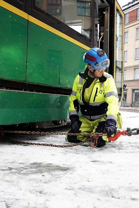 Kikkamiesten etumies Kari Kiiski testaa raitiovaunun kiskoille vetoa Töölön hallin pihassa.