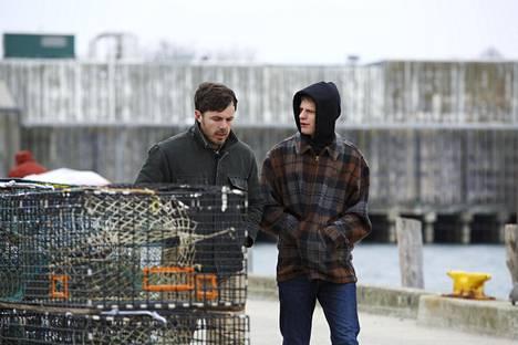 Huoltomies Lee Chandler (Casey Affleck, vas.) ottaa vastuuta veljenpojastaan (Lucas Hedges).
