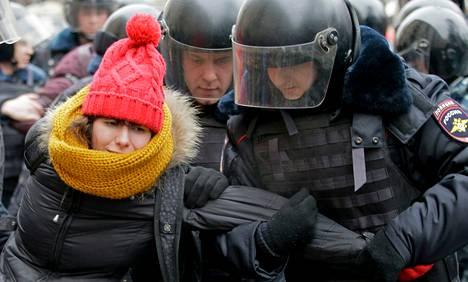 Poliisi otti kiinni mielenosoittajan oikeustalon ulkopuolella Moskovassa maanantaina.