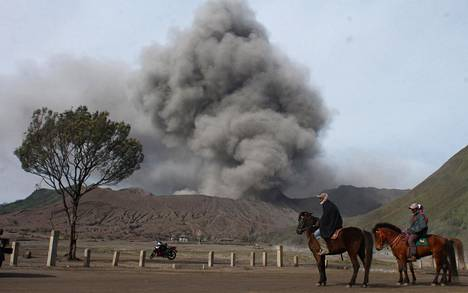 Hevosratsastajia katsomassa tulivuori Mount Bromon purkausta Probolinggossa Indonesiassa tiistaina.