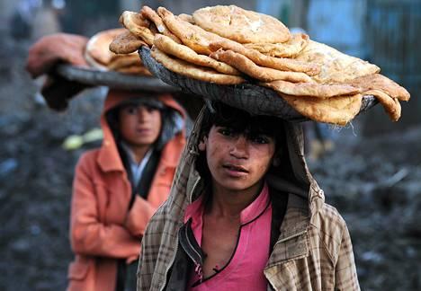 Afgaanilapset myivät leipää kadulla Kabulissa. YK on arvostellut maan heikkoa lainsäädäntöä, jonka pitäisi suojella naisia talibanien vallan murennuttua.