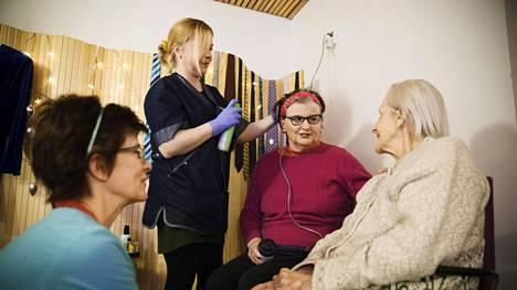 Sari Mustonen (vas.) rupattelee Margit Nylundin (oik.) kanssa Salasalongissa. Taustalla Jenni Tommila laittaa Marianne Kolkan hiuksia.