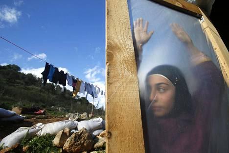 Syyrialainen pakolaistyttö seisoi oven takana leirillä Ketermayan kylässä Beirutin eteläpuolella. Kuva on vuodelta 2015.