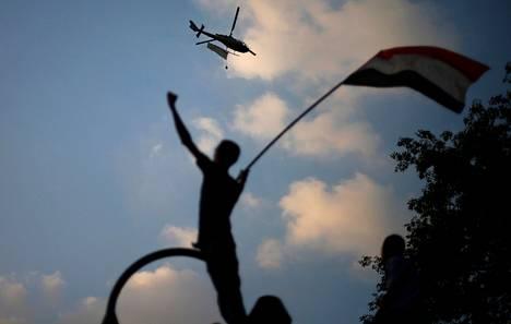 Armeijan helikopteri lensi Tahririn aukion yllä Kairossa maanantaina. Helikopteriin oli kiinnitetty Egyptin lippu.