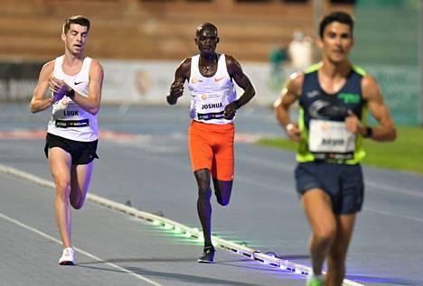 Joshua Cheptegein (kesk.) ennätysjuoksussa ratareunuksen valot näyttivät, onko hän ennätysvauhdissa.