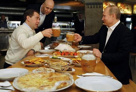 Dmitri Medvedev ja Vladimir Putin nostivat maljoja vapunpäivänä 2012.